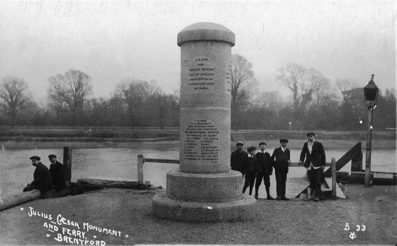 Inscribed cylindrical monument about 15-20' high, river in background