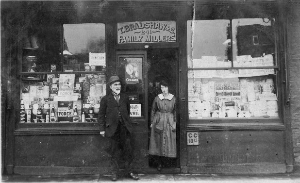 Couple standing in front of double-fronted shop 'T. Bradshaw 241 Family Millers'