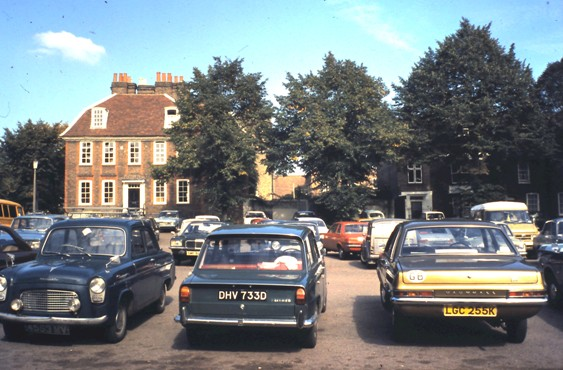 Colour photo showing cars parked in front of Georgian building
