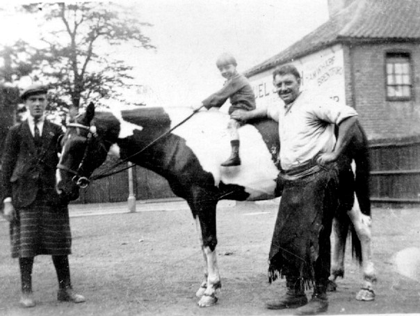 B/w photo, small boy on piebald horse whose head is held by an elderly man in a kilt; a cheery 40ish man with blacksmith's apron stands by the boy