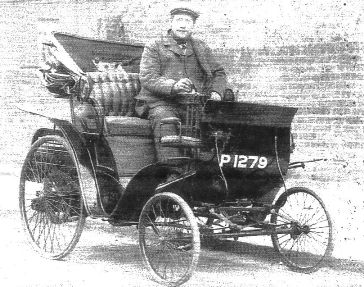 Early 20th century 2-seater car, front wheels smaller diameter than rear, with driver Thomas Dear