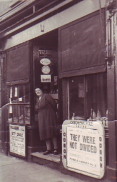B/w photo of  Alice Newman, shopkeeper, standing in the entrance to her novelties shop