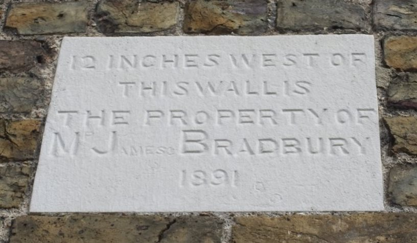 Plaque: 12 inches west of this wall is the property of Mr James Bradbury 1891