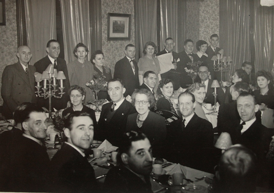 Around 25 people, men and wives, aged 30 - 60ish in a pub dining room