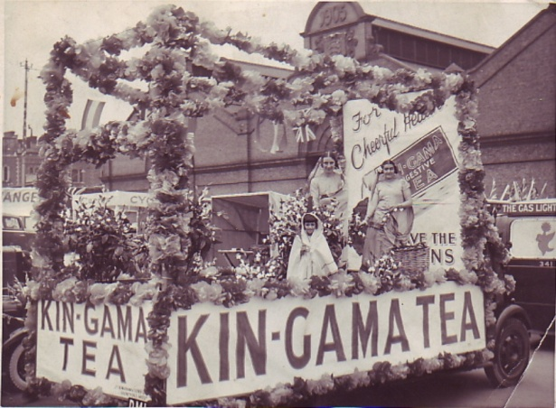 Garland-bestrewn float carrying two ladies and a small girl dressed as tea pickers in saris