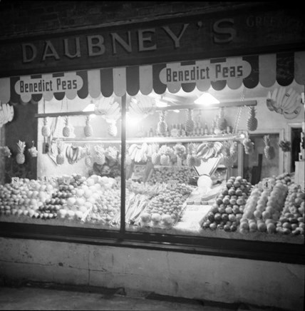 B/W photo taken in evening, showing greengrocers shop display