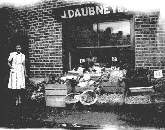 B/W photo taken outside shop, display of fruit and veg in wood boxes and wicker baskets