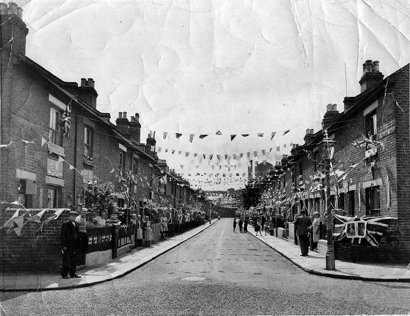 View along street festooned with bunting and union jacks, several residents standing in their front gardens