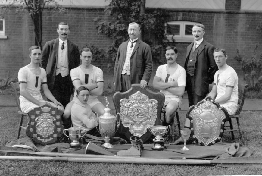Four rowers, club officials and trophies