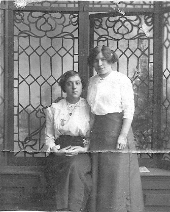 Mary Ellen Ryan (standing) with female work colleague in front of ornate leaded window