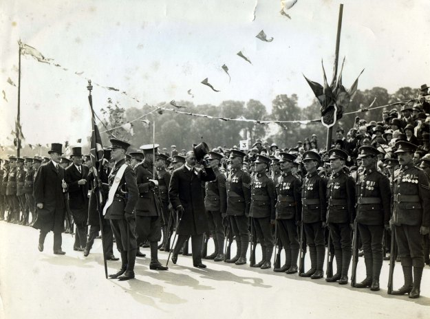 King George V inspecting a line of soldiers of various ranks, with flags and bunting in the background; the public are seated in tiers behind