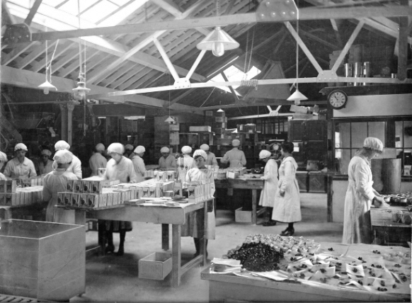 Originally sepia photo of packing room, approaching 20 women in white protective below knee long-armed clothing with white hats (like shower caps) packing goods on wooden tables; the packing room is single storey, no windows but skylights bring in light