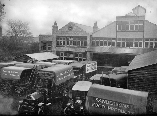 Originally sepia photo from 1921 showing transport yard full of motor lorries and horsedrawn delivery wagons, each with 'Sanderson Food Products' on the side