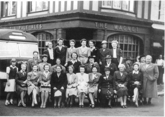 Group of 27 ladies standing by a coach