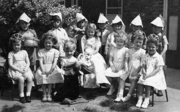 Small children, boys wearing pointy paper hats, girls wearing small tiaras