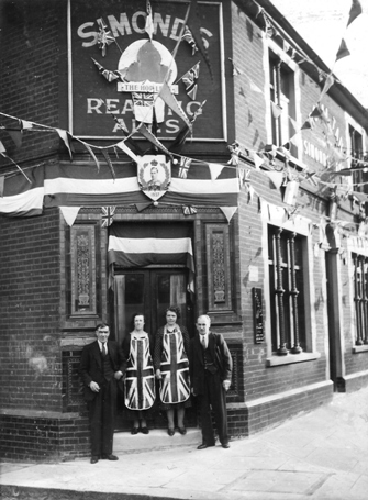 Two couples standing outside the Royal Tar, bunting, flags, Union Jack aprons for the ladies, celebrating King George VI coronation 1937