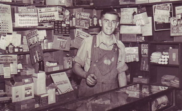 B/w photo of Stanley Newman at the counter, with an array of items pinned up behind him