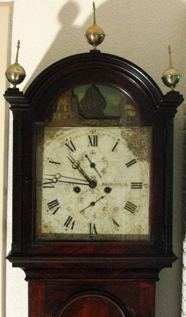 Early 19th century longcase clock; the ship goes back and forth over the dials