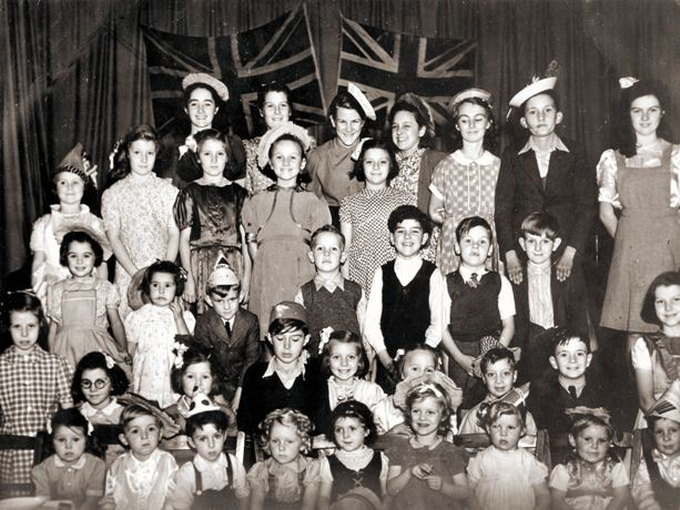 Photo of around 40 children on a stage, from tots to young teens, 2 Union Jacks behind