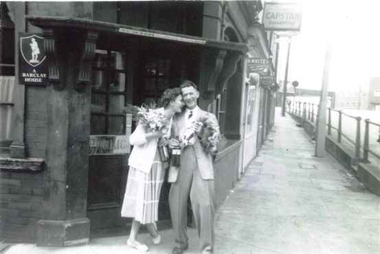 Happy couple with flowers outside a pub